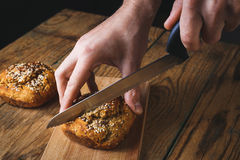 Man slicing bread on a wooden board Stock Photography