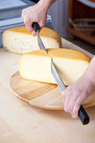 Man slicing cheese. Worker slicing the cheese using double handed cheese knife Stock Photo