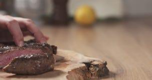 Man slicing cooked medium rib eye steak on board. Wide photo Royalty Free Stock Images