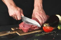 Chef cutting filet mignon on wooden board. Man slicing filet mignon on wooden board at restaurant kitchen. Chef preparing fresh meat for cooking. Modern cuisine royalty free stock photo
