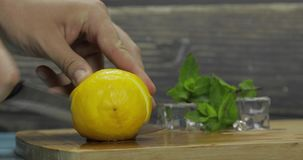 Man slicing lemon on a wooden cutting board in the kitchen. Ice cubes and fresh mint leaves on background stock footage