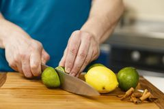 Man slicing limes and lemons. On a wooden board Stock Photo