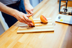 Man slicing orange in kitchen Stock Images