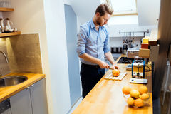 Man slicing oranges in kitchen Royalty Free Stock Photo