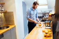 Man slicing oranges in kitchen Royalty Free Stock Photo