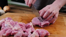 Man slicing pork meat on a table, working process closeup. Kitchen, knife. stock photography
