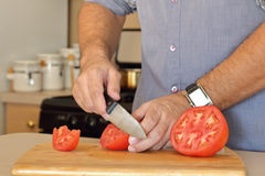 Man Slicing Tomato on Cutting Board. Slicing tomatoes by hand - no face Royalty Free Stock Image