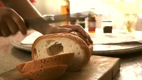 A man slicing a whole grain bread with a knife stock footage