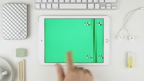 A man sliding green chroma key pictures on Apple iPad Air display at his desk