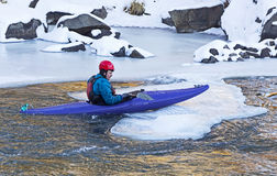 Man Sliding a Kayak On To Ice Stock Photography