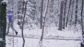 Man slingalöparespring i begrepp för för vinterskoginspiration och motivation utomhus lager videofilmer