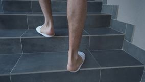 Man in slippers climbs the stairs