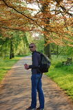 Man with a small backpack walks in spring park. Royalty Free Stock Images