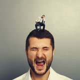 Man with small bored man on the head Stock Photography