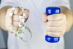 Man with small dumbbell and tape measure Royalty Free Stock Images