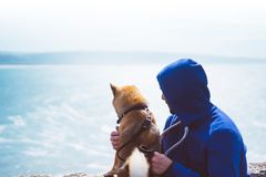 Man with small golden japanese shiba inu dog sitting togetherness on a mountain and looking at blue sea horizon, friends on relax royalty free stock photography