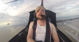 Man In Small Gyrocopter In Flight. Portrait of young man with pince-nez in small gyrocopter in flight stock footage