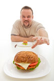 Man with small hamburger reaching for a bigger one Stock Image