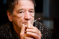 Man with small hypodermic needle Stock Images
