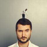 Man with small man on the head Stock Photography