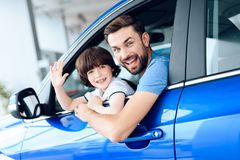 A man with a small son is sitting at the wheel of the car. Stock Photos