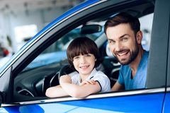 A man with a small son is sitting at the wheel of the car. Royalty Free Stock Image
