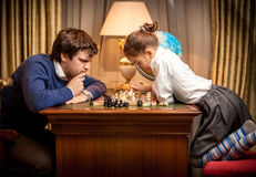 Man and smart little girl playing chess Stock Photos