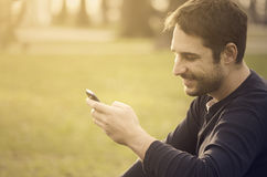 Man with smart phone. Young man sitting in the park and texting a message