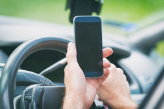 Man with smart phone in the car Stock Photography