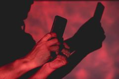 man with smart phone in hands on colorful background stock photography