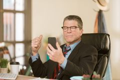 Man with Smart Phone in his office stock photography