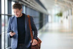 Man on smart phone - young business man in airport. Casual urban professional businessman using smartphone smiling happy inside office building or airport royalty free stock image