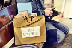 Man with a smartphone and a bag with the text happy black friday Royalty Free Stock Photography