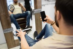 Man with smartphone at barbershop or hair salon. Grooming, technology and people concept - man with smartphone at barbershop or hair salon stock photos