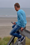 Man with smartphone at beach. Man sitting on a wooden balustrade at the beach checking his smartphone Stock Photography