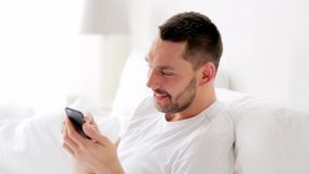 Man with smartphone in bed at home stock video