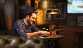 Man with smartphone and beer texting at bar Stock Image