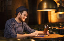 Man with smartphone and beer texting at bar Stock Images