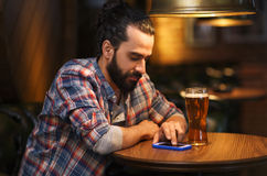Man with smartphone and beer texting at bar Royalty Free Stock Photos