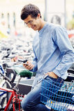 Man with smartphone and bicycle Royalty Free Stock Images