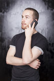 Man with smartphone calling someone. Young Man with smartphone, black background Stock Photo
