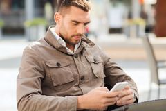 Man with smartphone at city street cafe Stock Photography