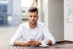 Man with smartphone and coffee at city cafe Royalty Free Stock Photography