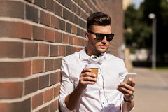 Man with smartphone and coffee cup on city street Royalty Free Stock Images