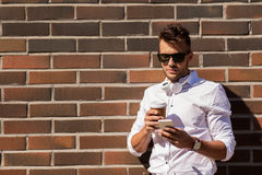 Man with smartphone and coffee cup on city street Stock Photos