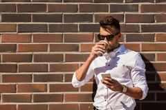 Man with smartphone and coffee cup on city street Royalty Free Stock Image
