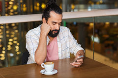 Man with smartphone and coffee at restaurant Royalty Free Stock Photo