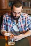Man with smartphone drinking beer at bar Royalty Free Stock Image