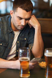 Man with smartphone drinking beer at bar Royalty Free Stock Images