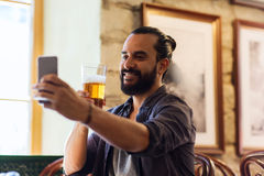 Man with smartphone drinking beer at bar or pub Royalty Free Stock Image